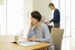 テーブルで雑誌を読むシニア女性の写真素材 [FYI02512974]