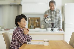 テーブルに座り笑顔のシニア女性の写真素材 [FYI02512984]