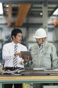 タブレットPCを見ながら打ち合わせをする作業員とビジネスマンの写真素材 [FYI02512993]