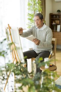 キャンバスに絵を描くシニア男性の写真素材 [FYI02513026]
