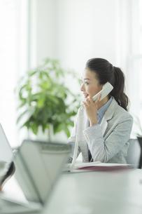 デスクで電話をするビジネスウーマンの写真素材 [FYI02513034]