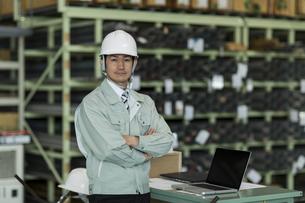 腕組みをする作業服の男性の写真素材 [FYI02513042]