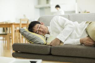 ソファーで昼寝をする男性の写真素材 [FYI02513058]