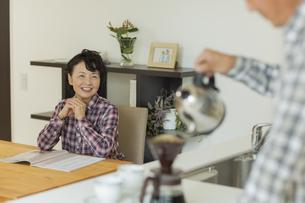 コーヒーを入れる夫を見るシニア女性の写真素材 [FYI02513069]