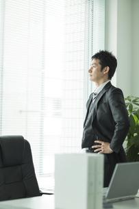 窓辺に立ち外を見るビジネスマンの写真素材 [FYI02513132]
