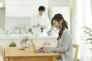 テーブルでパソコンをする女性の写真素材 [FYI02513192]