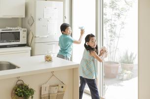 窓拭きをする兄と妹の写真素材 [FYI02513222]