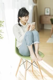 椅子に座って携帯電話を操作する女性の写真素材 [FYI02513229]