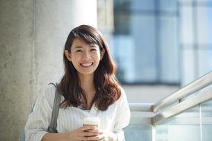 コーヒーを持って立つ笑顔の女性の写真素材 [FYI02513380]