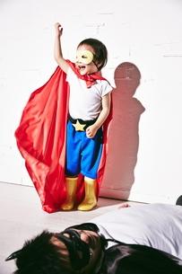 悪者をやっつけて勝利のポーズをするヒーローの男の子の写真素材 [FYI02515223]