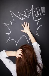 黒板に描かれた吹き出しの前で頭を抱えながら手を置く女性のイラスト素材 [FYI02515387]