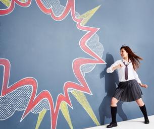 黒板に書かれた吹き出しの横でポーズをとる女子高生のイラスト素材 [FYI02515403]