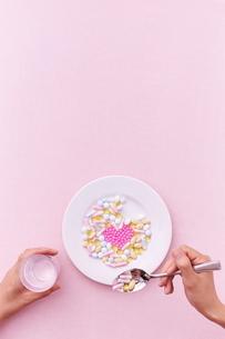 愛のサプリメントを食べようとする女性の写真素材 [FYI02515408]