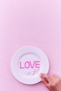 お皿に乗った愛のサプリメントを手に取る女性の写真素材 [FYI02515441]