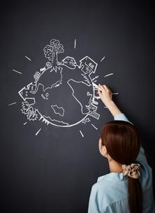 黒板に地球の絵を描く女性のイラスト素材 [FYI02515462]