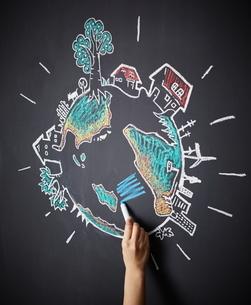 黒板に地球の絵を描く女性のイラスト素材 [FYI02515491]
