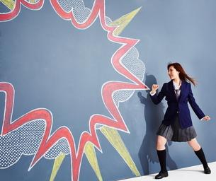 黒板に書かれた吹き出しの横でポーズをとる女子高生のイラスト素材 [FYI02515494]