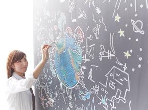 黒板に地球を描く女性のイラスト素材 [FYI02515555]