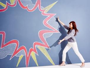 黒板に書かれた吹き出しの横でポーズをとっている女性のイラスト素材 [FYI02515632]