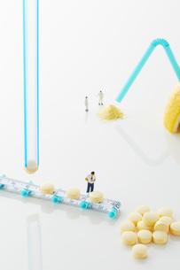 白い天板の上のレモンとビタミン剤とミニチュア人形の写真素材 [FYI02516123]