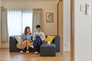 リビングでくつろぐ男女とソファに置かれたAIスピーカーの写真素材 [FYI02516183]