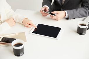 複数のデバイスを使ってお客さんと商談するサラリーマンの写真素材 [FYI02516822]