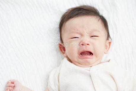 白いシーツの上で泣きそうになっている赤ちゃんの写真素材 [FYI02516826]