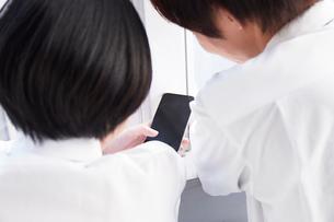 窓辺でスマートフォンを見る男子高生と女子高生の写真素材 [FYI02517123]