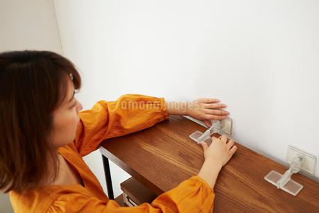 本棚に転倒防止グッズをつけている女性の写真素材 [FYI02517529]