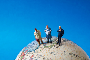 地球儀とビジネスマンのミニチュア人形の写真素材 [FYI02517696]