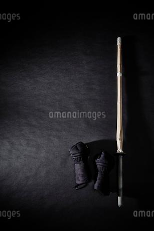 黒い背景に置かれた竹刀と甲手の写真素材 [FYI02517788]