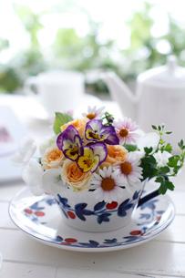 ティータイム、テーブルの上の花のアレンジとティーポットとカップ&ソーサー(生花)の写真素材 [FYI02517914]