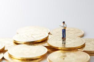 ビットコインの上のミニチュアのサラリーマンの写真素材 [FYI02518261]