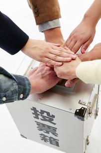 投票箱の上で円陣を組む人々の手の写真素材 [FYI02519071]