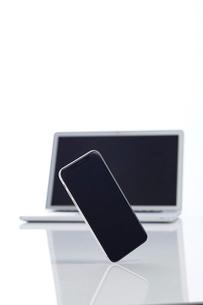 新しいスマートフォンと背景に置かれたノートパソコンの写真素材 [FYI02519108]