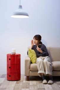 ソファーに座ってAIスピーカーに話しかける女性の写真素材 [FYI02519191]
