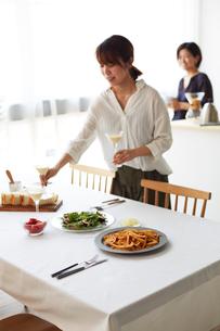 ホームパーティーのテーブルセッティングをする2人の女性の写真素材 [FYI02519468]