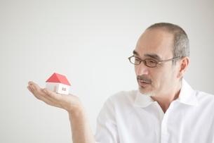 家の模型を見つめる男性の写真素材 [FYI02519577]