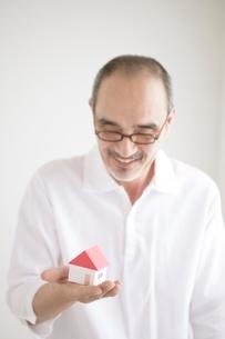 家の模型を持つ男性の写真素材 [FYI02519905]