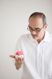 家の模型を見つめる日本人男性の写真素材 [FYI02520226]