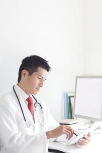 タブレットPCを操作する男性医師の写真素材 [FYI02520401]