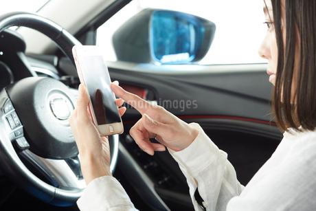 運転席でスマートフォンを操作する女性の写真素材 [FYI02520577]