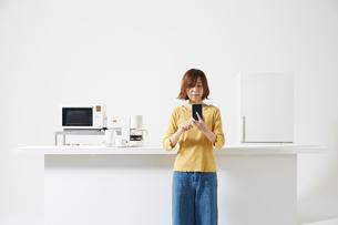 キッチンでスマートフォンを操作する女性の写真素材 [FYI02520580]