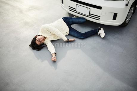 車の前に倒れている男性の写真素材 [FYI02521866]