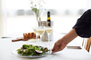 セッティングされたテーブルにサラダを出す女性の手の写真素材 [FYI02522358]
