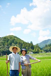 水田の前で農具をもつ男女の写真素材 [FYI02523204]
