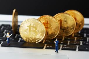 キーボードの上に立てられたビットコインとミニチュアの写真素材 [FYI02523215]