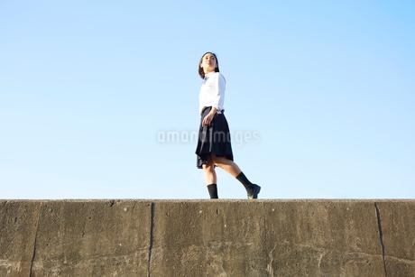 堤防の上を歩く女子高生の写真素材 [FYI02523278]