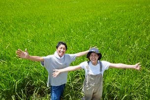 水田の前で両手を広げる笑顔の男女の写真素材 [FYI02523378]