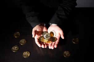 ビットコインを持ったスーツを着た男性の写真素材 [FYI02523788]